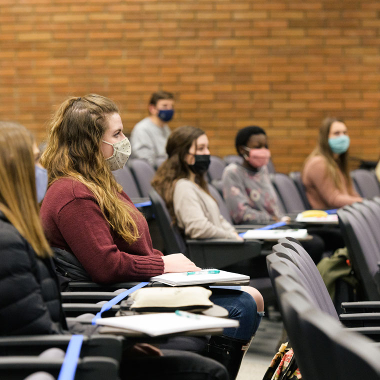 Socially distanced students wear masks in class on the first day of the spring semester.